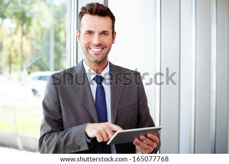 Happy businessman standing with laptop in office - stock photo