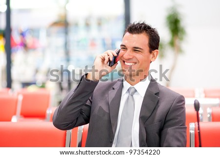 happy businessman talking on cell phone at airport - stock photo