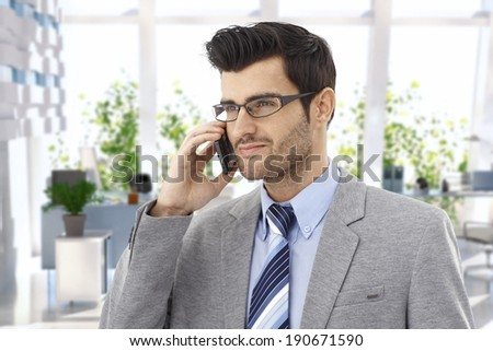 Happy businessman talking on cellphone at office. - stock photo