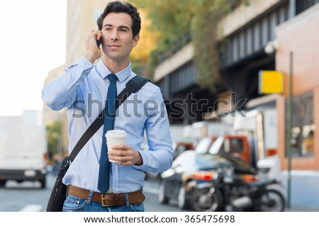 Happy businessman talking on the mobile phone. Young businessman communicating over cell phone while holding a paper cup and walking on the road. Smiling guy at smart phone while going to work.  - stock photo