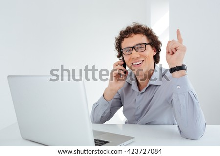 Happy businessman talking on the phone at his workplace  in office - stock photo