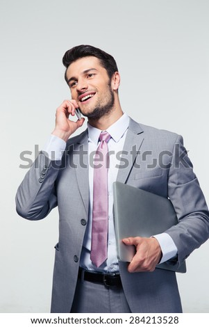 Happy businessman talking on the phone over gray background. Looking away