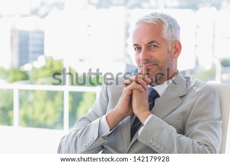 Happy businessman thinking in his office - stock photo