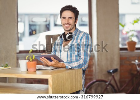 Happy businessman using digital tablet while standing by table in creative bright office