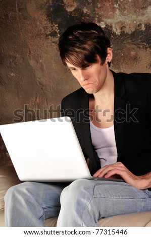 Happy businessman using laptop at his grunge apartment