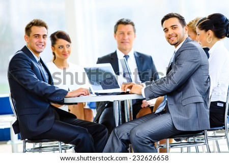 Happy businessman using laptop in business building, smiling. - stock photo