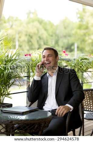 Happy businessman using mobile phone at outdoor summer restaurant - stock photo