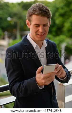 Happy businessman using mobile phone outdoors