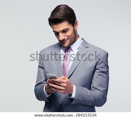 Happy businessman using smartphone over gray background - stock photo