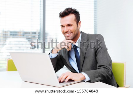 Happy businessman wbrowsing web on his laptop in the office - stock photo