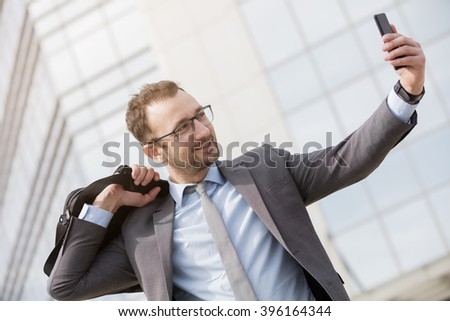 Happy businessman with a bag over his shoulder taking selfie outdoors    - stock photo