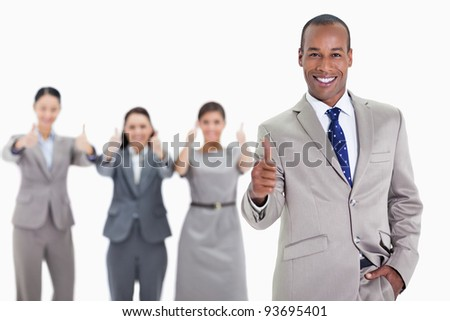 Happy businessman with a hand in his pocket and approving with co-workers in the background with thumbs up - stock photo