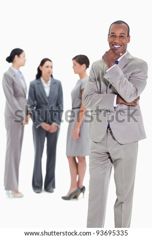 Happy businessman with a hand on his chin and three co-workers talking seriously in the background - stock photo