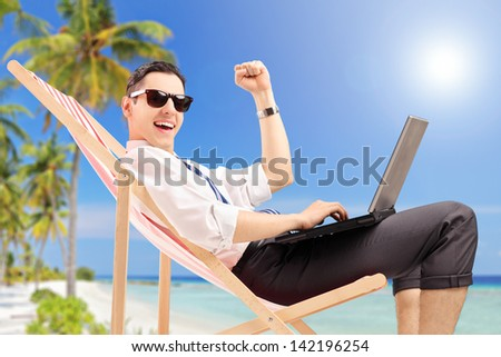 Happy businessman with a laptop on a tropical beach - stock photo
