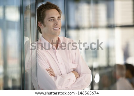 Happy businessman with arms crossed leaning on office glass door - stock photo