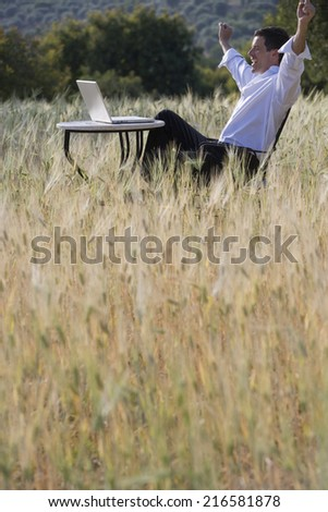 Happy businessman with arms raised looking at laptop on table in rural field - stock photo