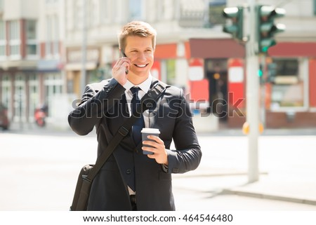 Happy Businessman With Coffee Cup Talking On Mobile Phone