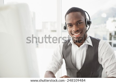 Happy businessman with headset interacting in his office - stock photo