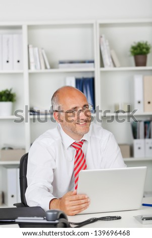 happy businessman with laptop looking to side - stock photo