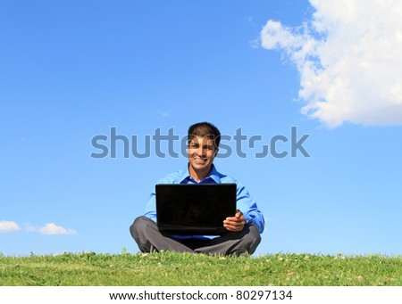 happy businessman with laptop, outdoor against blue sky