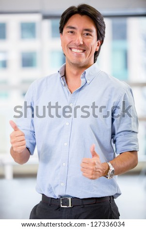 Happy businessman with thumbs up at the office - stock photo