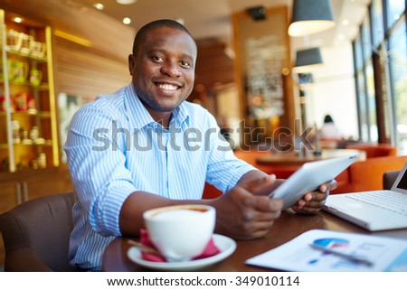 Happy businessman with touchpad drinking coffee at cafe - stock photo