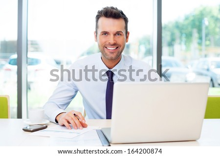 Happy businessman working at the office on laptop. - stock photo