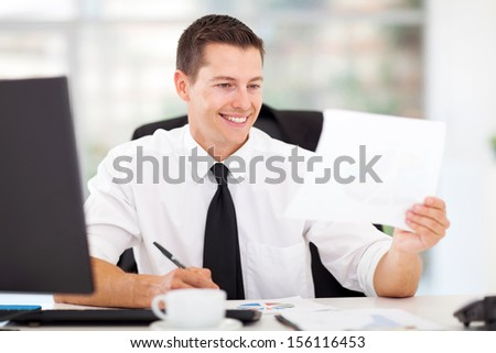 happy businessman writing report in his office