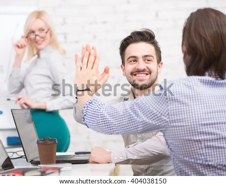 Happy businessmen clasping hands in office while their colleague lady doing presentation on new business strategy in office. - stock photo