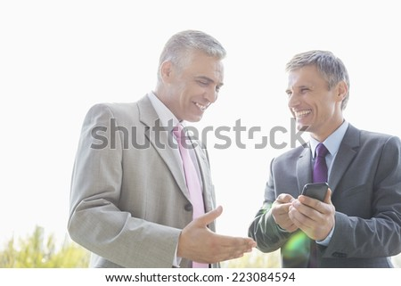 Happy businessmen discussing over mobile phone outdoors - stock photo