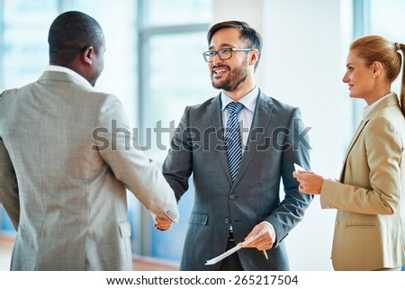 Happy businessmen handshaking after striking deal - stock photo