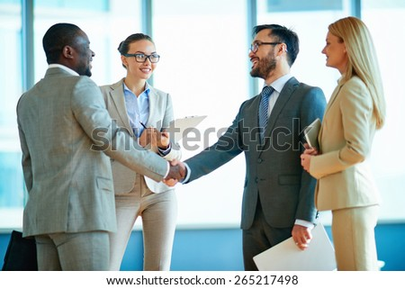 Happy businessmen handshaking with their two colleagues near by - stock photo