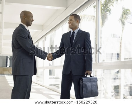 Happy businessmen shaking hands while standing in office corridor - stock photo