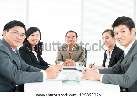 Happy businessmen sitting at table and smiling