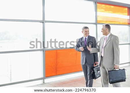 Happy businessmen talking while walking in railroad station - stock photo