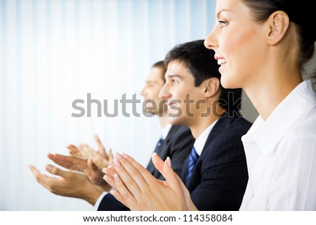 Happy businesspeople applauding at office - stock photo
