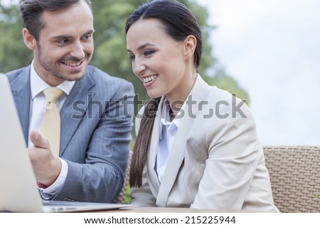 Happy businesspeople discussing over laptop outdoors - stock photo