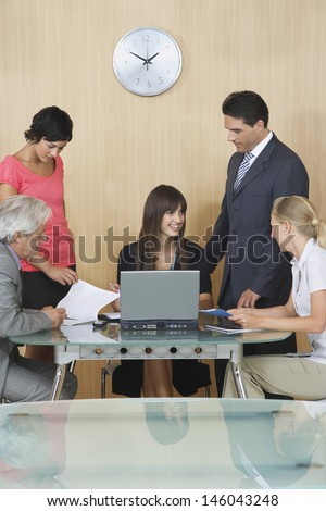 Happy businesspeople having meeting with laptop in conference room - stock photo
