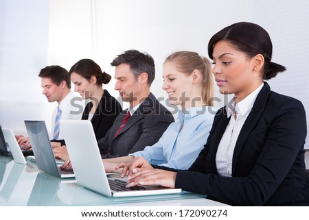 Happy Businesspeople In A Row Working Together At Office