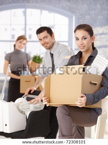 Happy businesspeople moving to new office, packing boxes, smiling.? - stock photo