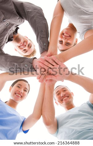 Happy businesspeople placing their hands top of each other - stock photo