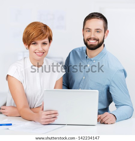 Happy businesspeople standing in meeting room, working on laptop