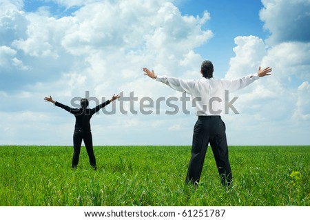 happy businesspeople standing on green grass and looking up