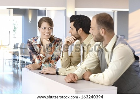 Happy businesspeople talking at office, businesswoman smiling. - stock photo