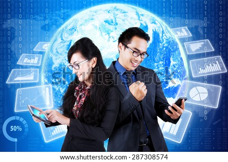 Happy businesspeople using cellphone in front of world map background with financial graph on the futuristic interface