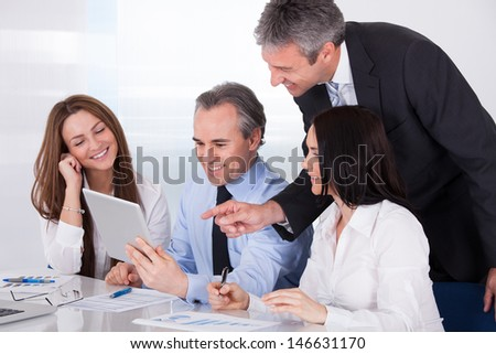 Happy Businesspeople Using Digital Tablet In Office
