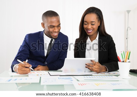 Happy Businesspeople Working On Digital Tablet With Graphs On Desk - stock photo
