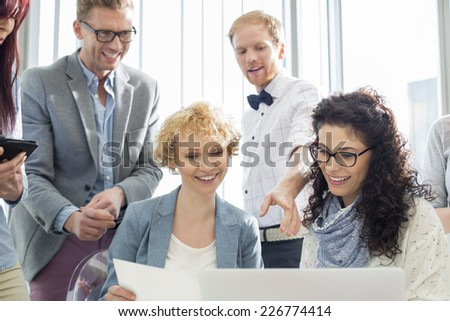Happy businesspeople working on laptop in creative office - stock photo
