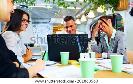 Happy businesspeople working together around the table in office - stock photo