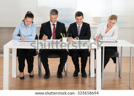Happy Businesspeople Writing On Clipboard At Desk - stock photo